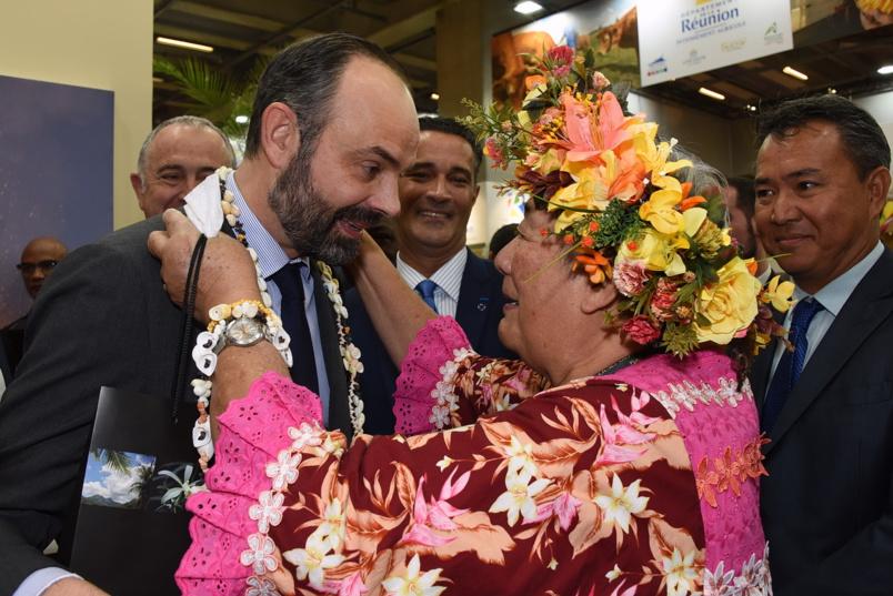 """Les Polynésiens l'ont """"poursuivi"""" sur le stand de La Réunion pour lui mettre une couronne de fleurs... sous l'oeil amusé de Stéphane Bijoux"""