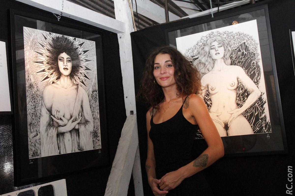 Belly, illustratrice, devant deux de ses oeuvres
